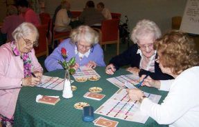 Elderly people filling in the awards cards